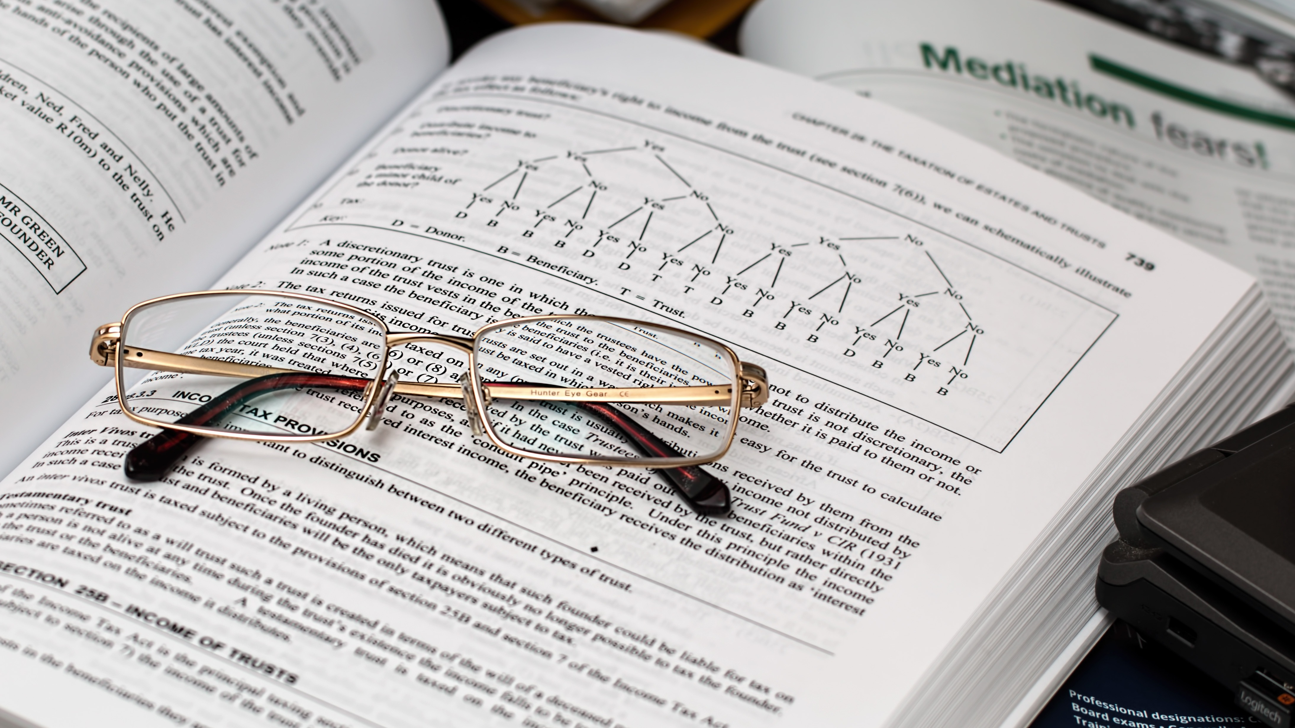 A pair of glasses on an open text book