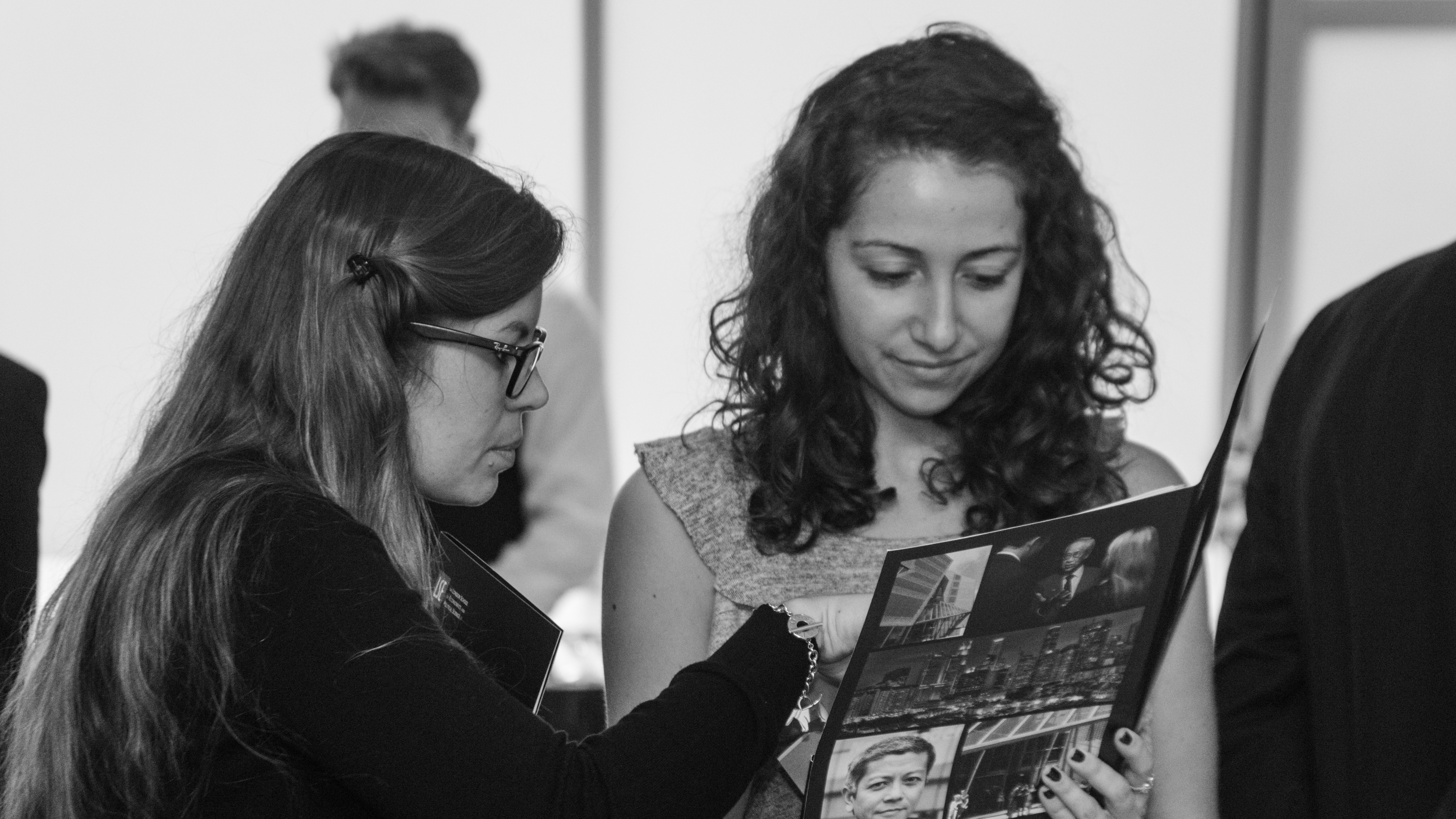 Two women examining an LSE SEAC conference pack