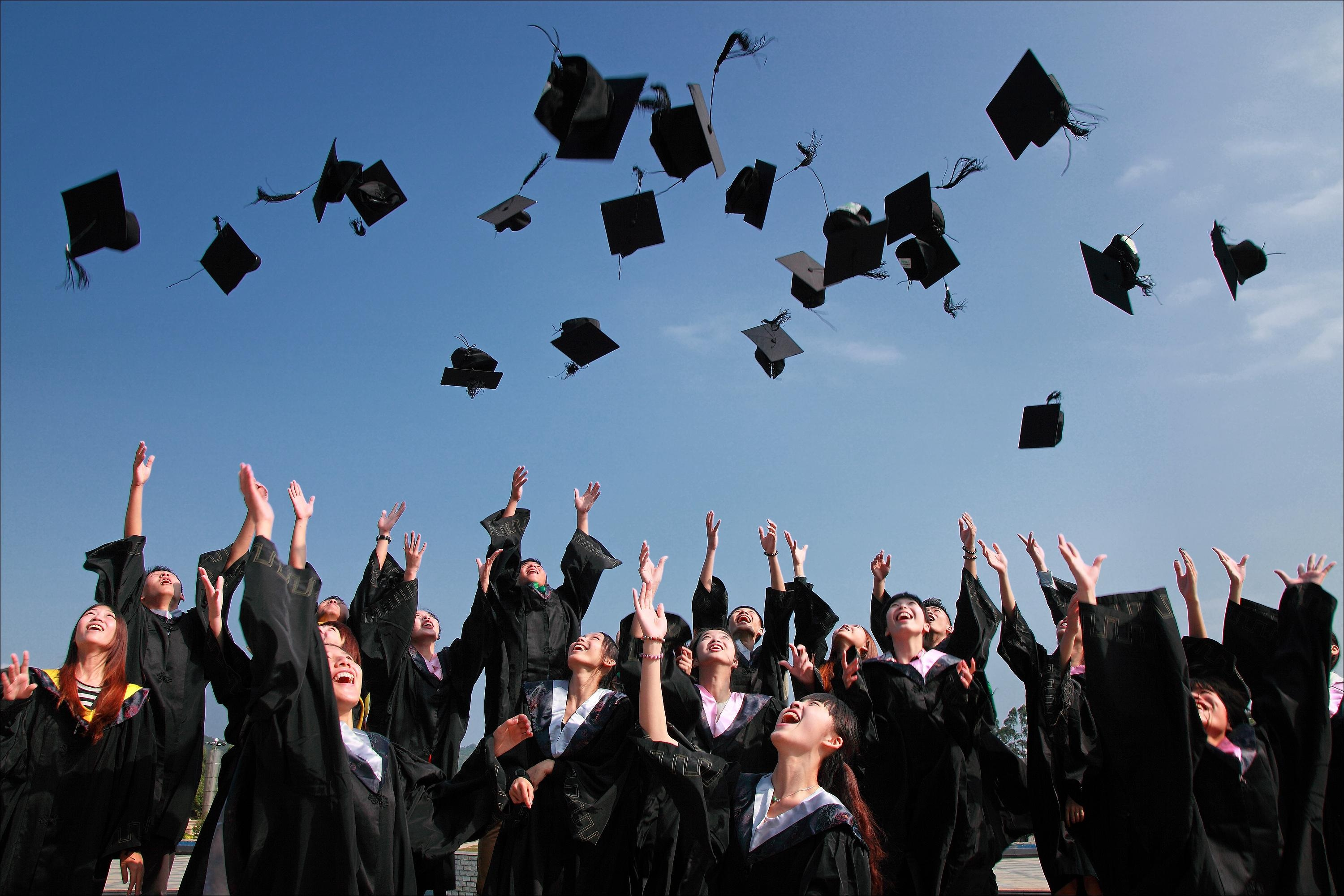 Graduates throwing their mortarboards in the air
