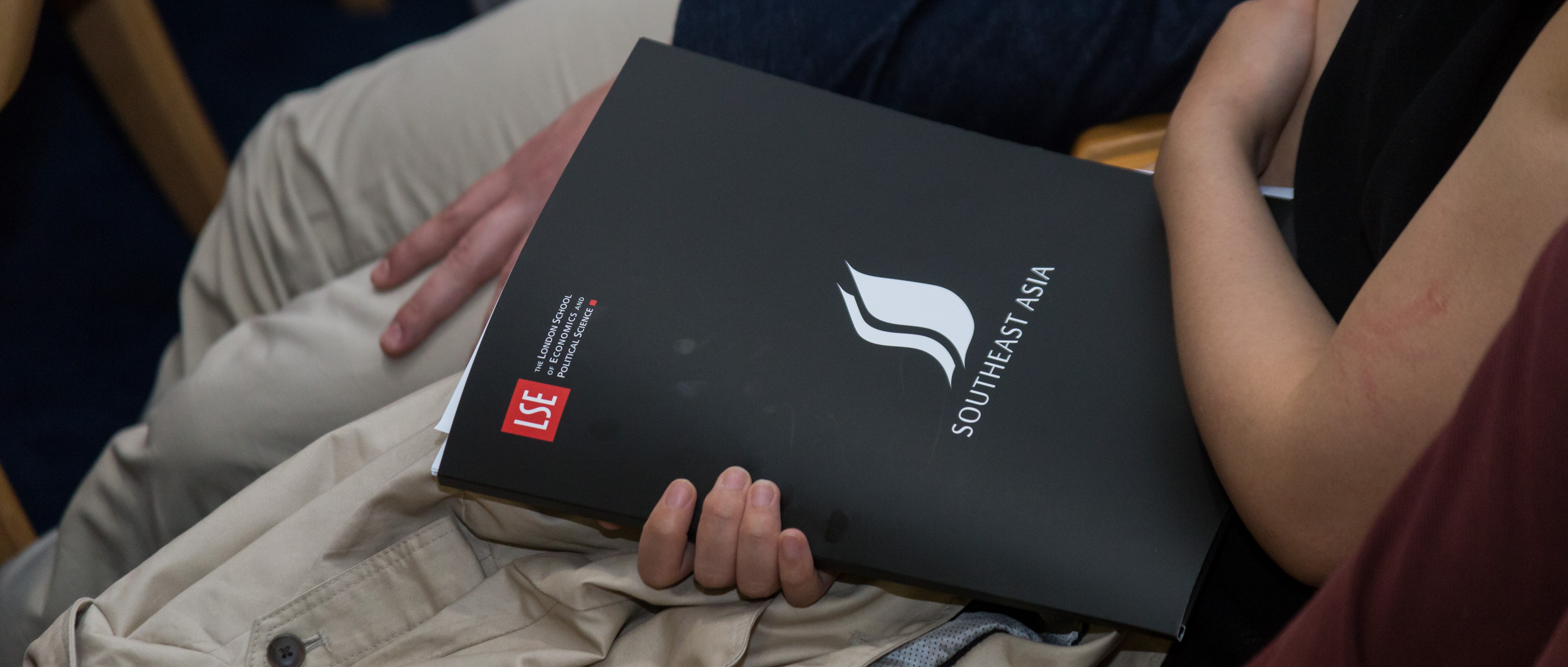 An audience member holding a branded LSE SEAC conference pack