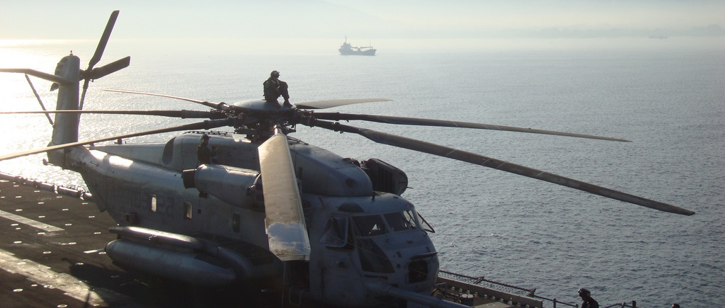 A military helicopter landed on a ship at sea