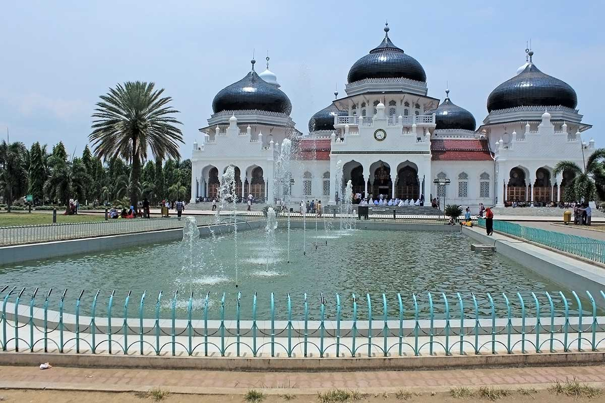 An ornate Indonesian mosque by a water pool