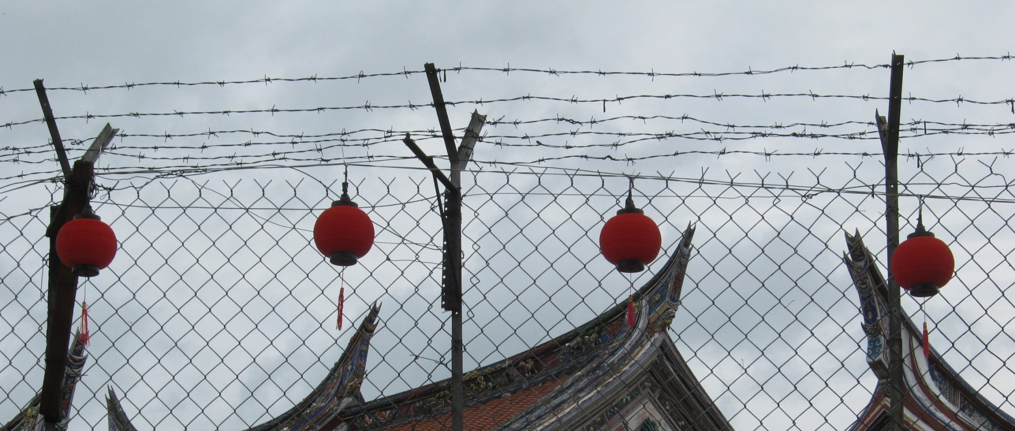 Red lanterns hanging on a barbed wire fence