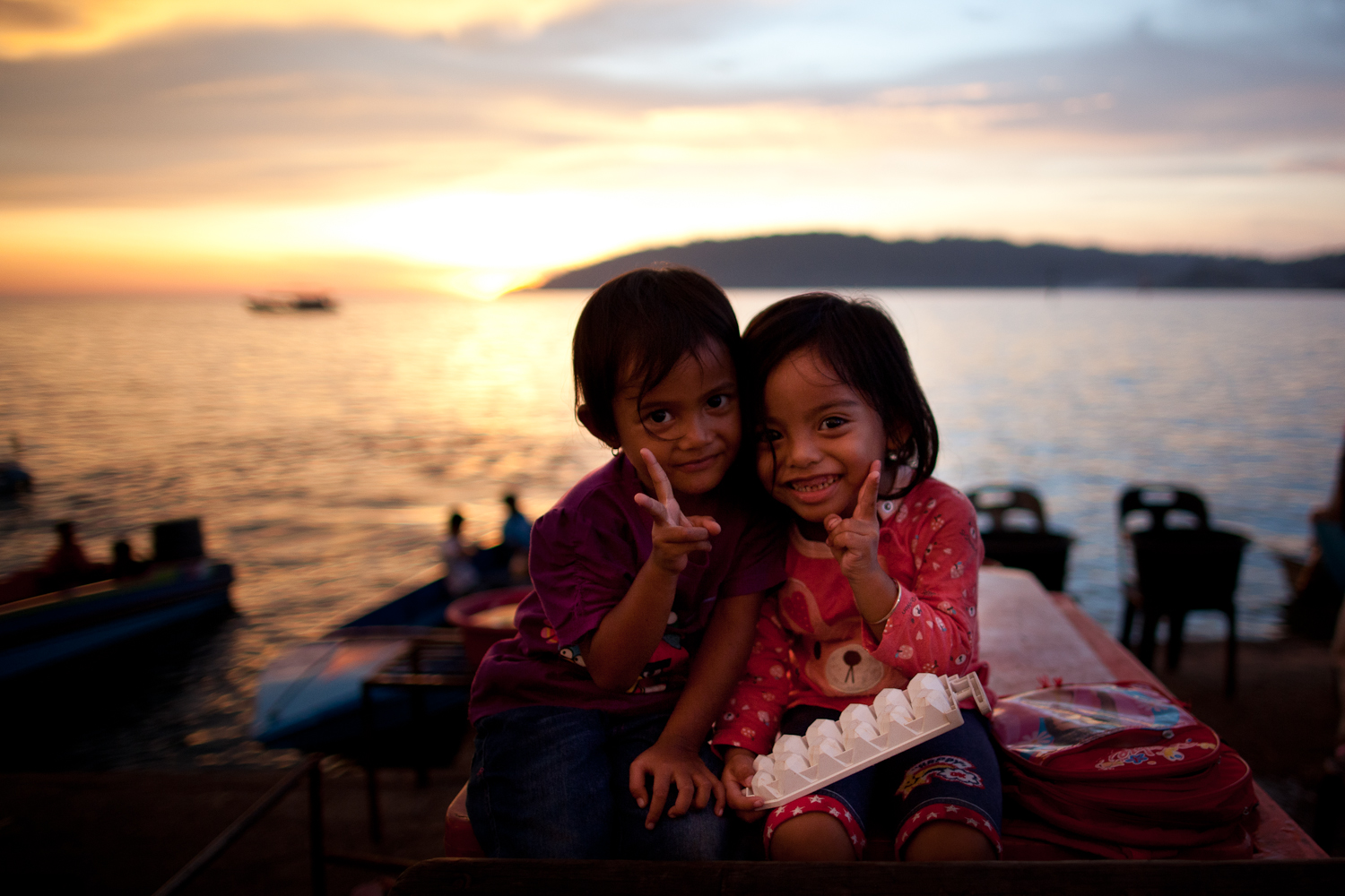 Two children doing peace signs by the sea at sunset