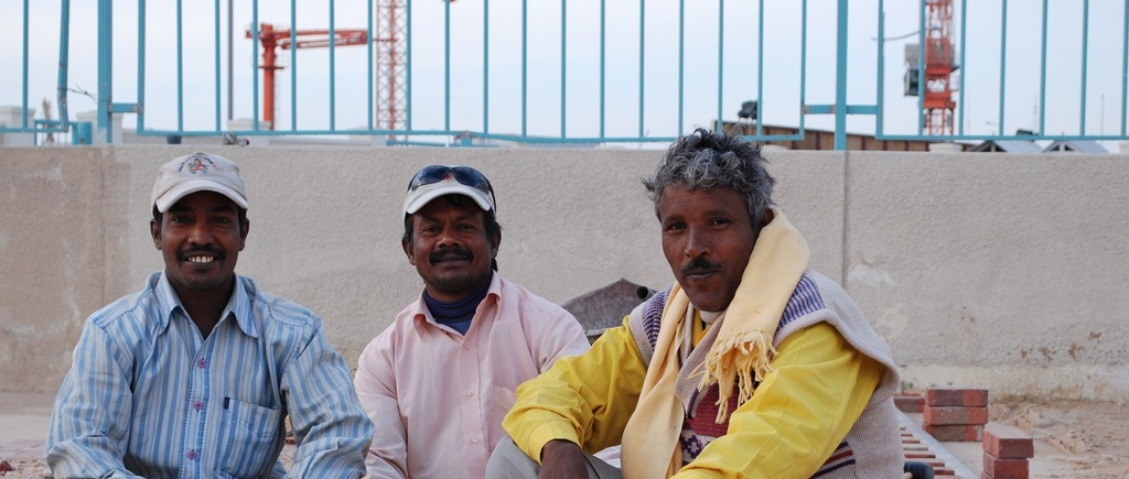 Three Middle Eastern migrants by a contruction site