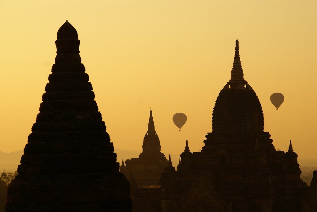 Three temples and two hot air balloons silhouetted against a yellow sky