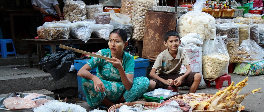 A mother and son selling goods at a street market in Yangon