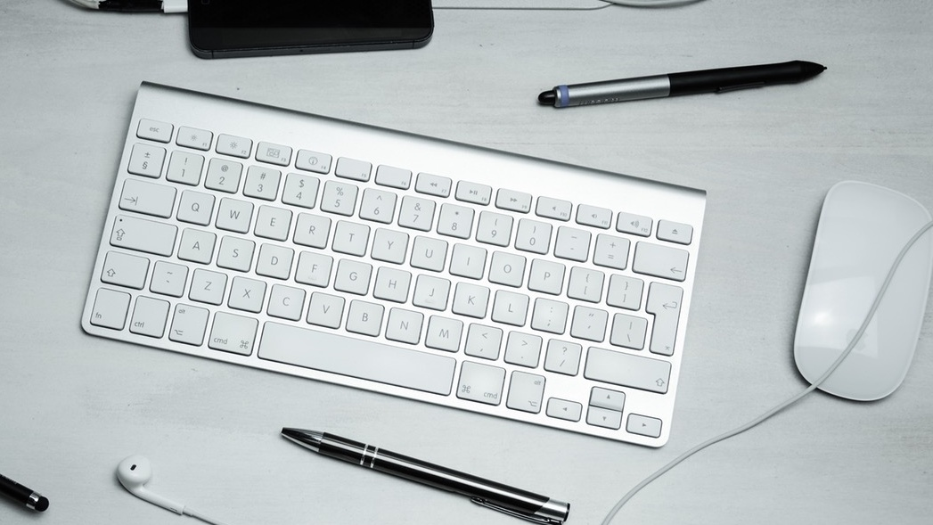 A keyboard, pens and a mouse on a desk