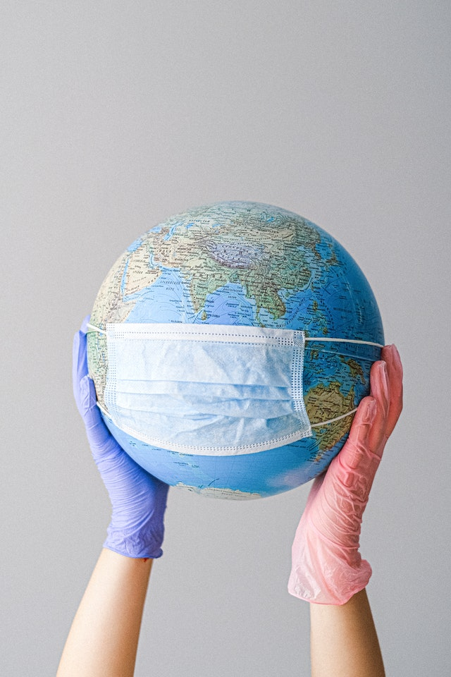 hands-with-latex-gloves-holding-a-globe-with-a-face-mask-4167544