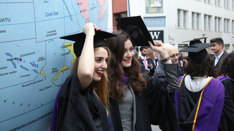 Two women students get a photo taken of themselves in their graduation gowns and caps beside Mark Wallinger's 'World Turned Upside Down'