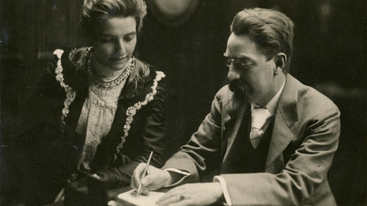 Sidney Webb writes in a book as Beatrice looks over his shoulder
