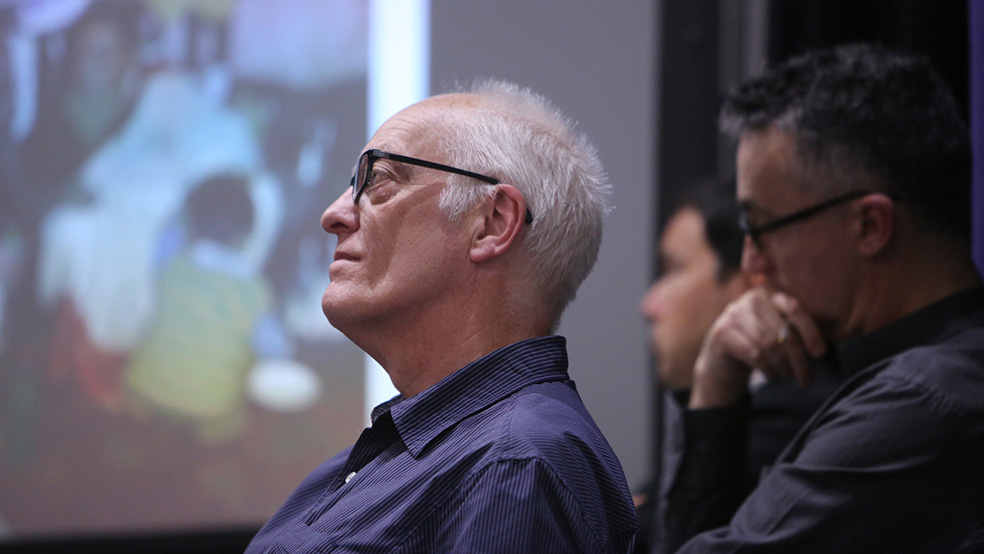 A white haired man with glasses listens to a lecture